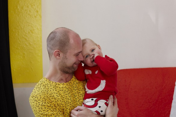 Geel witte muur, rode bank, man en profile met gele blouse, zoon op de arm in rood pakje.