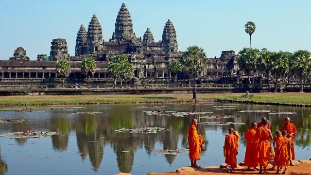 Grijs bouwwerk, met blauw water en figuren in oranje gewaden