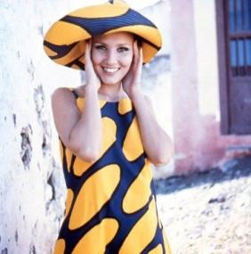 Vrouw met gele en blauwe jurk en dito hoed