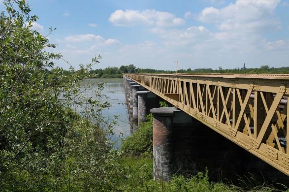 Boven/zijaanzicht okergele spoorbrug Moerputten over moeras