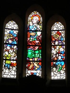 Sint Jozef als beschermer van de mensheid die onder zijn rode mantel schuilt. Glas in de Jozefkapel van de nieuwe Bavo te Haarlem, van Humbert (W.F.M.C.) Randag. Foto Stephan van Rijt 2007.