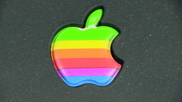 Achtergrond zwart, midden appel met hap eruit, en horizonrale balken in groen, rood blauw