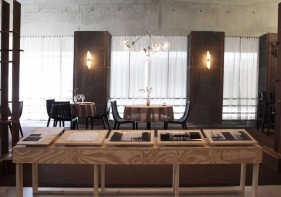 Beige , grenen houten tafel, tapekleurige muurdelen met gelige verlichting, witte vitrage, zwarte stoelen, beige tafels