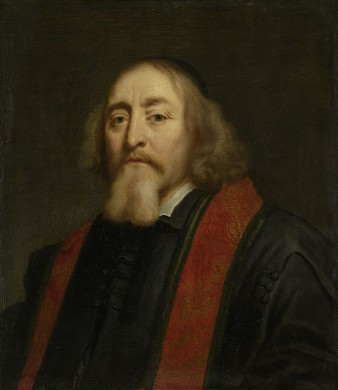 Man halflang rossig haar, dito baard, zwarte jas, rode biezen, achtergrond, grijs