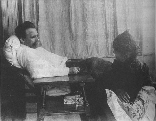 zwart wit, liggende man zijaanzicht, witte blouse, zwarte broek, tafeltje met glas water, vrouw aan zijn zijde