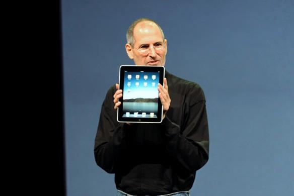 Man zart gekleed met bril tegen grijze achtergrond, in zijn had een  Ipad