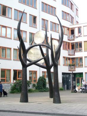 Grijs kunstwerk van bomen, tegen grijze achtergrond van plein en  gebouwen