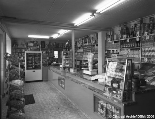 Grijs, wit zwart interieur met ttonbank en veel flesjes, potjes en een weegschaal