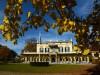 groenstrook bruine vlekkejm geel wit huis, 4 ramen met zwarte luiken, blauwe strook bovenin, bruingele bladeren bovenin