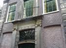 Rechthoekige facade, roodbruin, zwarte rechthoekige deur en dito raam